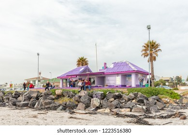 MELKBOSSTRAND, SOUTH AFRICA, AUGUST 19, 2018: A beach scene in Melkbosstrand in the Western Cape Province. A kiosk, toilets and people are visible