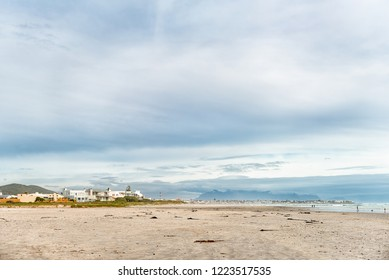 MELKBOSSTRAND, SOUTH AFRICA, AUGUST 19, 2018: A beach scene in Melkbosstrand in the Western Cape Province. Buildings, people and Table Mountain are visible