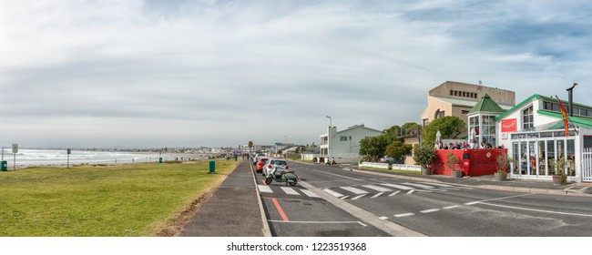 MELKBOSSTRAND, SOUTH AFRICA, AUGUST 19, 2018: A street scene, with restaurant, vehicles and people, at the beach in Melkbosstrand in the Western Cape Province
