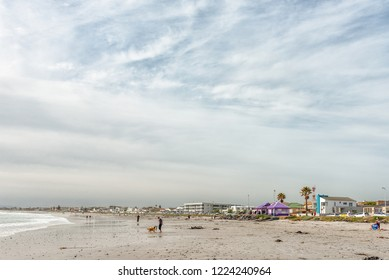 MELKBOSSTRAND, SOUTH AFRICA, AUGUST 19, 2018: A beach scene in Melkbosstrand in the Western Cape Province. Buildings, a dog and people are visible
