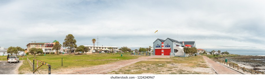 MELKBOSSTRAND, SOUTH AFRICA, AUGUST 19, 2018: A beach scene, with restaurants, businesses and people, in Melkbosstrand in the Western Cape. The building of the National Sea Rescue Institute is visible