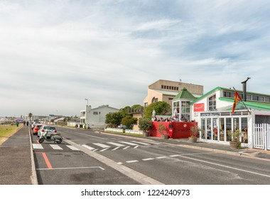 MELKBOSSTRAND, SOUTH AFRICA, AUGUST 19, 2018: A street scene, with restaurant, vehicles and people, in Melkbosstrand in the Western Cape Province.