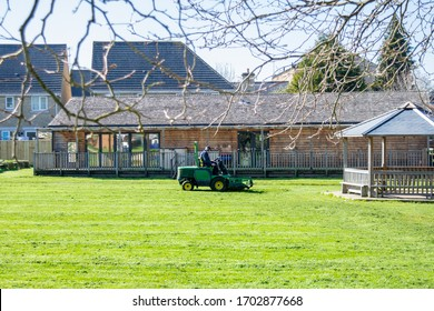 Melksham Wiltshire UK March 25 2020 A man on a ride on  lawnmover cutting the grass of a primary school field  while the children are not at school