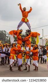 Mellahalli, Karnataka, India - November 1, 2013: Karnataka Rajyotsava Parade. Orange and white clad male acrobats form pyramid in front of drum band. Silver sky.