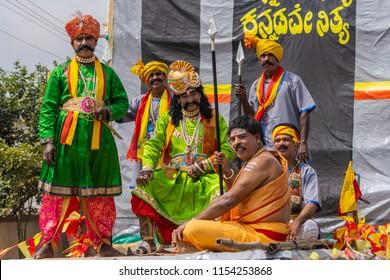 Mellahalli, Karnataka, India - November 1, 2013: Karnataka Rajyotsava Parade. Six men display traditional colorful clothes from different regions in the State under the slogan Kannada for ever.