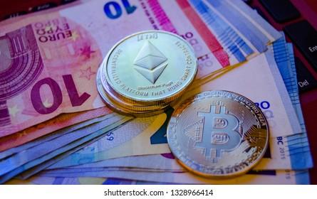 Mellieha, Malta 02.03.2019 - bitcoin and ethereum phisical coins over euro monete - money exchange for virtual coins- buy and sell bitcoin ethereum concept