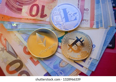 Mellieha, Malta 02.03.2019 - bitcoin litecoin and ethereum phisical version of virtual coins over the euro paper money buying and seling virtual currency concept