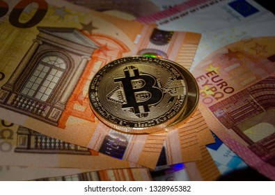Mellieha, Malta 02.03.2019 - bitcoin phisical version of virtual coin over euro bank notes.