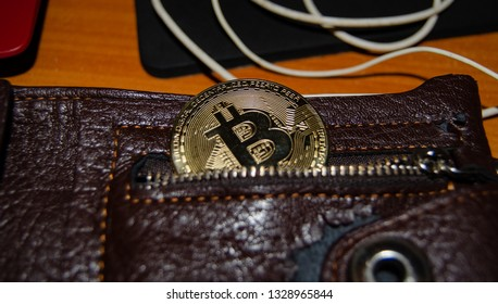 Mellieha, Malta 02.03.2019 - bitcoin phisical version of virtual currency half in the pocket of wallet virtual currency wallet concept