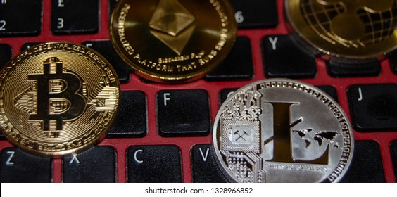Mellieha, Malta 02.03.2019 - different virtual monetary phisical coins on keyboard, bitcoin, litecoin, ethereum and ripple virtual currency exchange concept