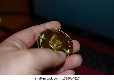 Mellieha, Malta 02.03.2019 - woman hand holding ethereum, close up phisical coin - ethereum, blockchain technology concept