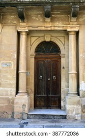 MELLIEHA, MALTA - JANUARY 27. Entrance to a residential house with portico and wooden door in Mellieha, Malta