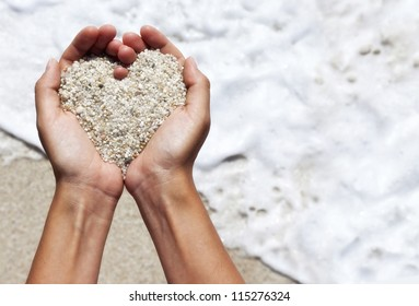 Mellow heart shaping female hands above beach