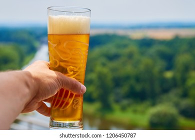 Melnik, Czech Republic - July 6, 2017: A fresh pint of Czech cold beer on a terrace in Melnik, historic city near Prague with the Labe and Vltava rivers on the background on hot summer afternoon.