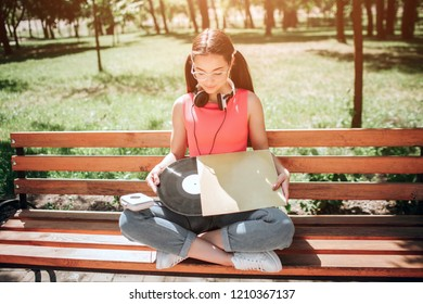 Melomaniac girl is holding a vynil and cover from it in her hands. She is looking at it. Girl is siiting on bench with her legs crossed.