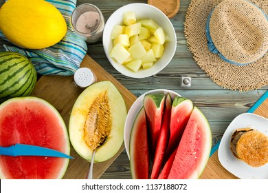 Melon buffet on a wooden picnic table with whole, halved and sliced refreshing juicy watermelon and canary melon viewed from above in a full frame still life with a straw sunhat