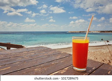 Melon juice on a sea beach. Glasses with red drink and straw stands on a fallen coconut. Exotic fruit refreshment beverage on a tropical vacation.