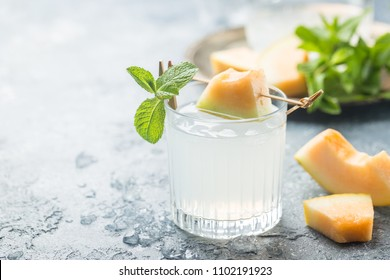 Melon lemonade with ice and mint in a glass on the gray table. Summer refreshing drink.