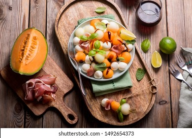 Melon, mozzarella, prosciutto appetizer or snack, summer salad with cantaloupe melon with glass of wine on wooden background top view, antipasti, italian food
