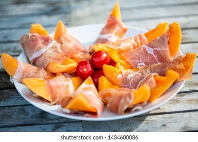 Melon with parma ham on garden table