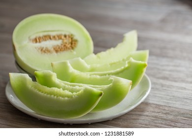 Melon sliced and served on white colored plate on a wooden table