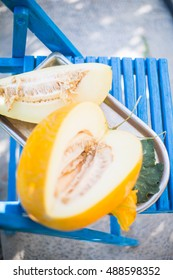 Melon sliced in vintage tray on blue wooden chair against garden background