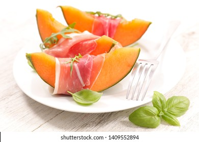 melon slices and prosciutto ham with basil