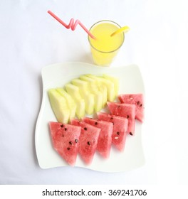 Melon and watermelon slices on plate and a glass of lemonade