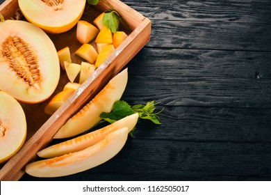 Melon in a wooden box. Sliced to pieces of melon. On a wooden background. Free space for text. Top view.
