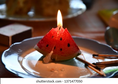 Melted candle shaped like triangle piece of watermelon. Candlelight flame closeup. Burning fire of candle on vintage plate with burnt matches nearby. Shadows from candle lights at retro utensils.