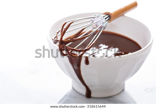 Melted chocolate in a bowl with a whisk