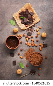 Melted chocolate, cocoa powder, chocolate slices, nuts and mint on a dark rustic background. Top view, flat lay.