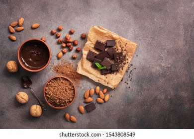 Melted chocolate, cocoa powder, chocolate slices, nuts and mint on a dark rustic background. Top view, flat lay, copy space
