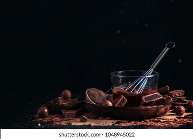 Melted chocolate glazing in a glass cup with a whisk. Dark chocolate and milk chocolate chunks with cinnamon and other spices on a black background.