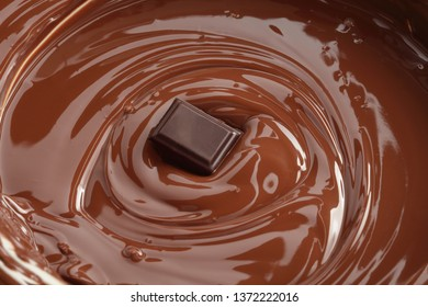 Melted chocolate swirl  background  with a piece of chocolate in the center