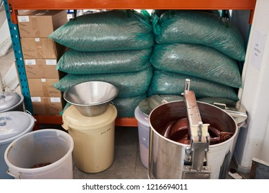 Melted chocolate turning in a large stainless steel mixer and bags of cocao beans on shelves in an artisanal chocolate making factory