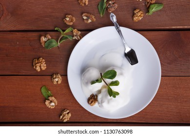 melted ice cream on a plate, decorated with mint and walnuts