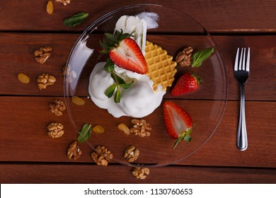 melted ice cream in transparent bowl, decorated with strawberries and biscuit