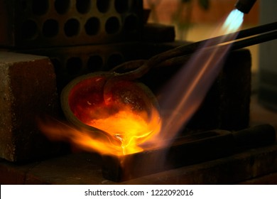Melted silver pellets in a red hot melting pot being casted into a silver ingot with the help of a blowtorch, with beautiful orange flames