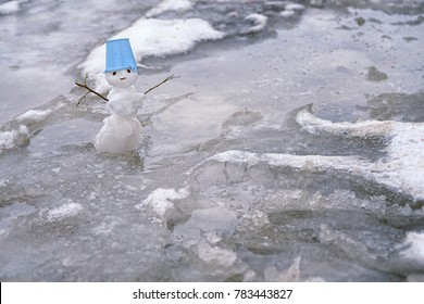 melted small snowman in  puddle. bad warm rainy winter weather.  anomaly weather