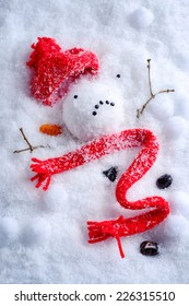 Melted snowman with knitted hat and scarf