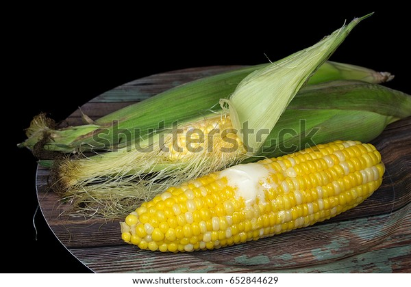 melting butter on cooked corn on the cob with raw corn on wood grain plate