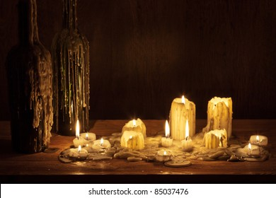 Melting candle in wooden shelf with bottle