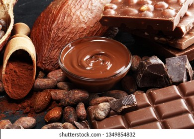 Melting chocolate or melted chocolate with a chocolate swirl and stack, chips and powder on dark table