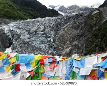 Melting Glacier in the clouds among green hills in Mingyong, Yunnan, China, and Buddhist prayer flags on the top of the mountain.