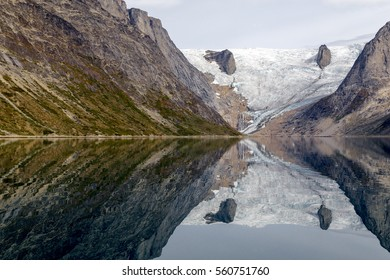 A melting glacier in the south of Greenland is reflected in the calm waters of the fjord creating a mirror effect