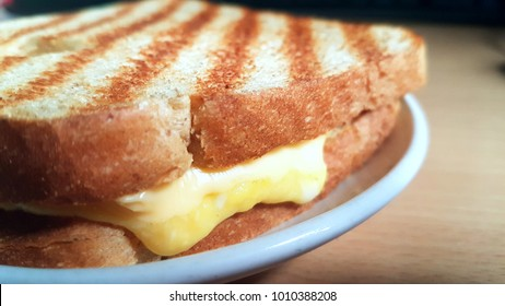 melting grilled cheese sandwich on white plate and wooden table