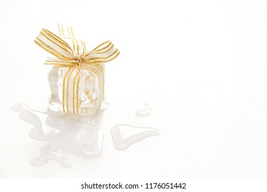 Melting Ice cube gift  and drops on white table