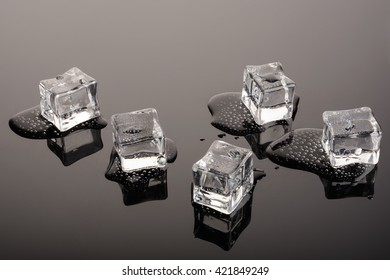 Melting ice cubes on mirror surface. Cristal. Transparent