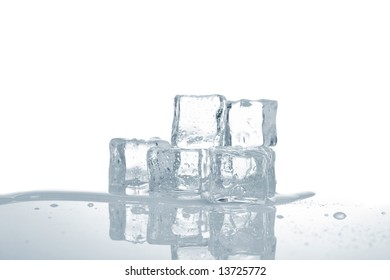 Melting ice cubes in water reflected on white background. Shallow depth of field